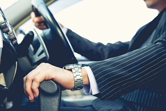 Man In Suit With Hands On The Wheel